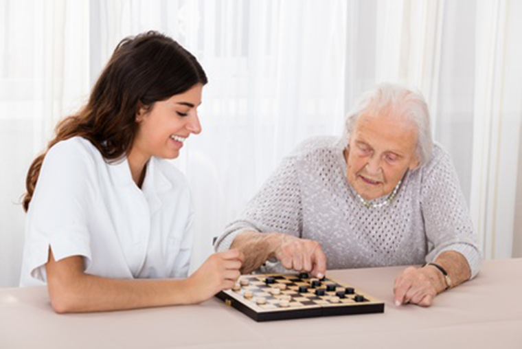 Pflegerin spielt mit Seniorin Schach